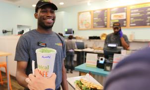 Employee handing a guest a smoothie