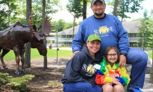 family in front of a moose statue