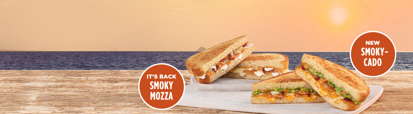 New Smoky-Cado Grilled Cheese Sandwich and Smoky Mozza Grilled Cheese Sandwich on cutting boards and in front of a sunset.