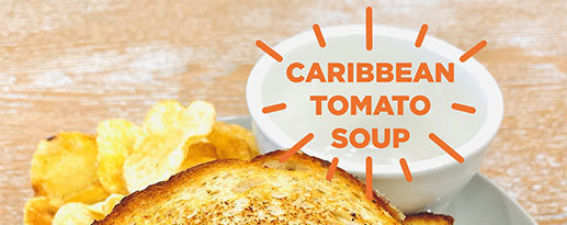 Empty bowl next to a grilled cheese sandwich with the text Caribbean tomato soup