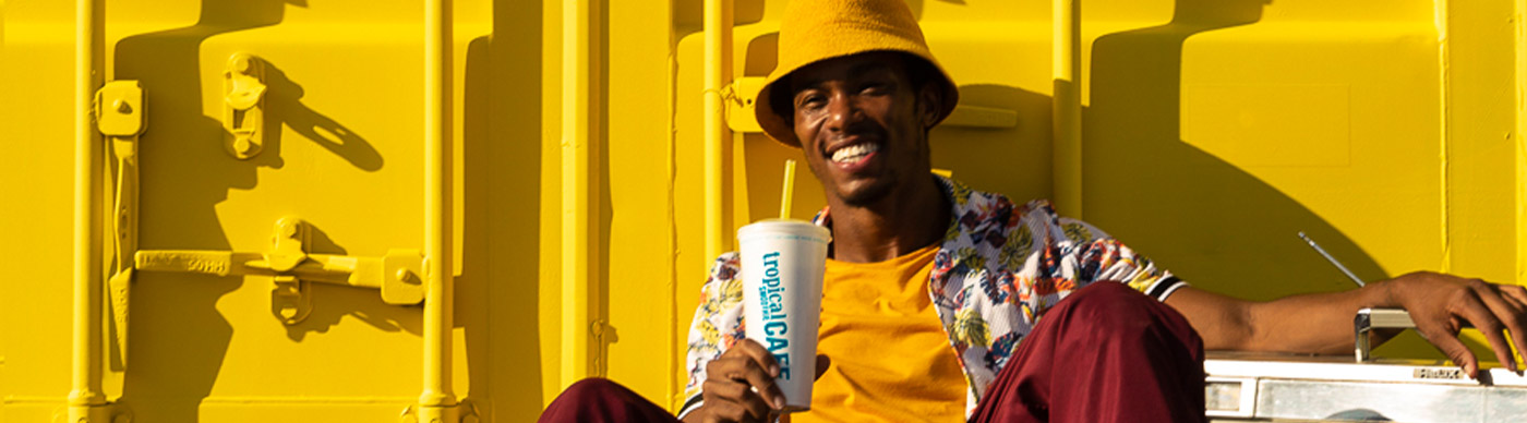 A smiling man holding a smoothie while sitting in front of a shipping container